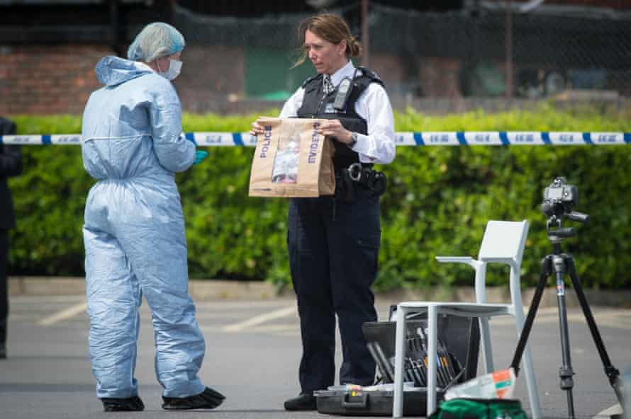 Police and forensic officers holding an evidence bag, at the scene at a car park in Hampton.
