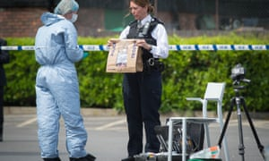 A police officer holds an evidence bag at the scene of a stabbing in west London in May.