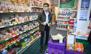 Rishi Sunak dons a face mask in a shop on the Isle of Bute, in Rothesay, Scotland.