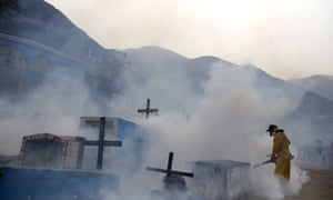 A health worker carrying out fumigation as part of preventive measures against the Zika virus and other mosquito-borne diseases at a cemetery on the outskirts of Lima.
