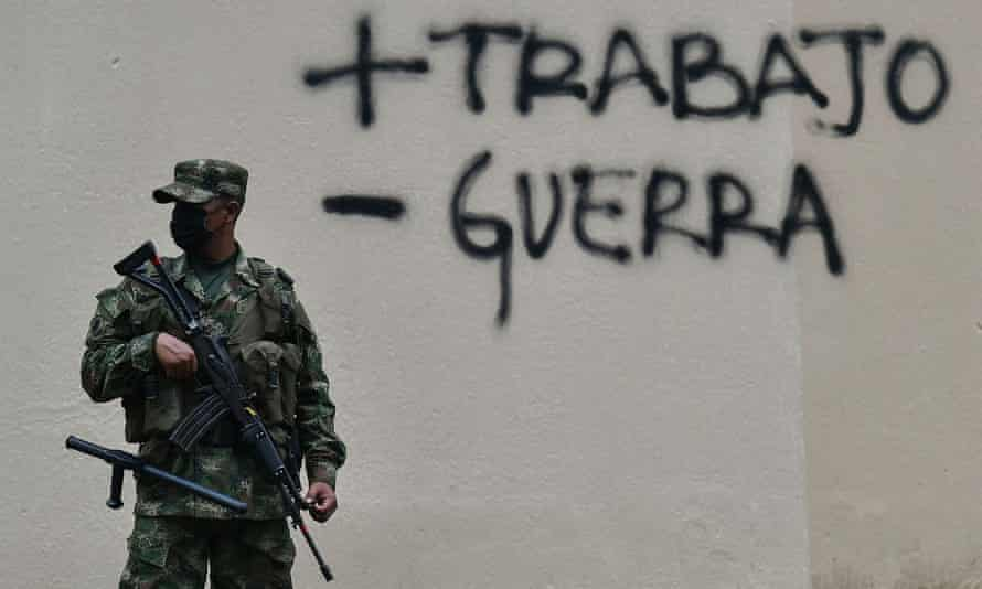 A soldier stands guard in front of graffiti saying plus trabajo,  minus guerra
