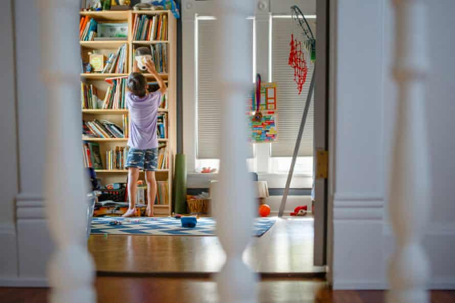 A child reaching for a toy on a high shelf (mounted photo).