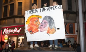 Two people hold up a banner saying 'Theresa the appeaser'