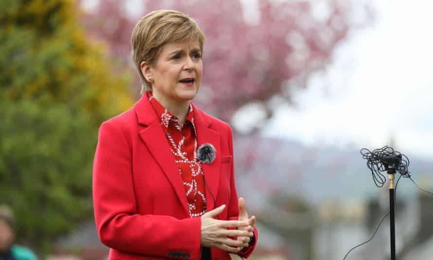 Nicola Sturgeon outdoors in a red coat, speaking into a microphone