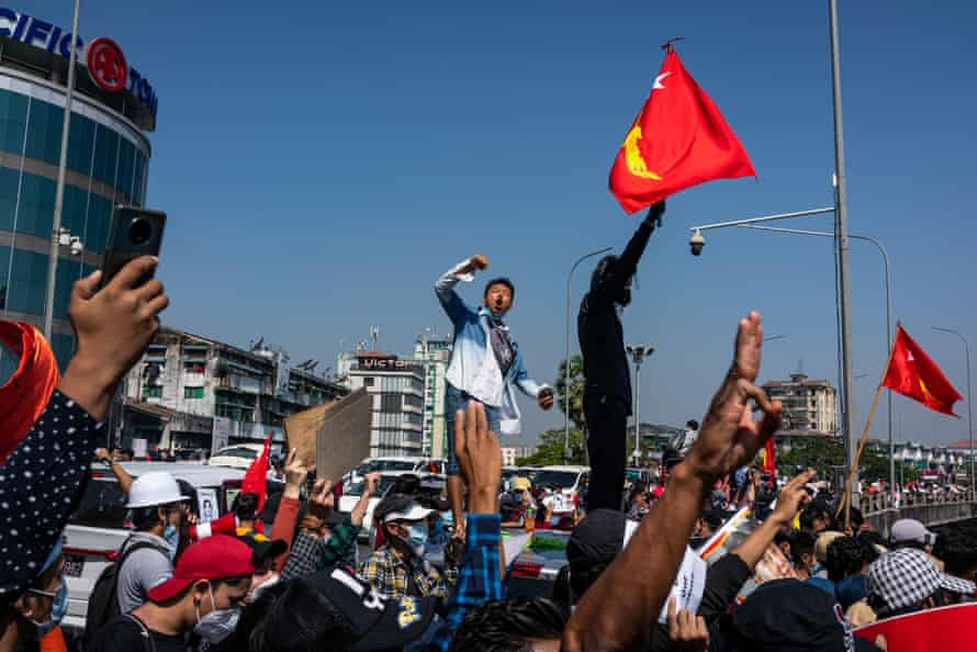 Protesters wave red National League For Democracy (NLD) flags and raise three-finger salutes in Yangon