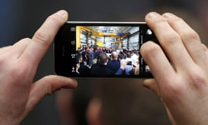 Ed Miliband seen through a phone camera at a visit to an engineering company in Huddersfield