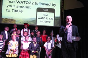 Pastor Bruce Stoke of Woodgrange Baptist Church, London, addresses the audience after a Watoto Choir performance, in front of a screen calling for donations