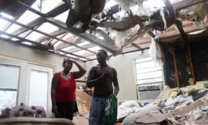Latasha Myles and Howard Anderson stand in their living room where they were sitting when the roof blew off around 2:30am as Hurricane Laura passed through the area on August 27, 2020 in Lake Charles, Louisiana.