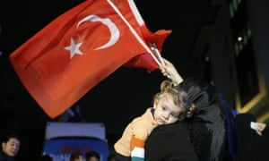 A supporter of Turkey's ruling Justice and Development party holds a baby as she waves Turkish flags in Istanbul on Sunday.