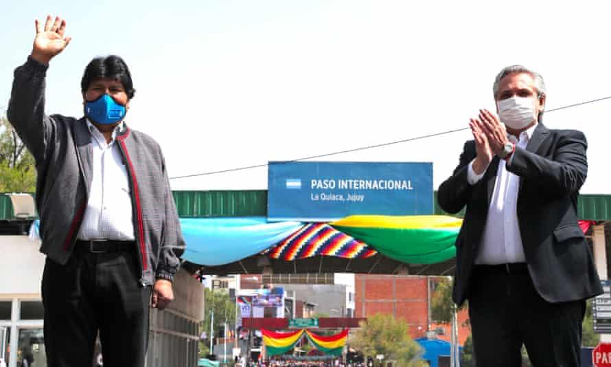 Evo Morales, left, waves goodbye next to Argentina's president, Alberto Fernández, in La Quiaca, Argentina, on 9 November.