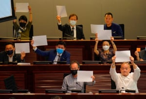 Pro-democracy lawmakers raise white papers to protest during a meeting to discuss the new national security law at the Legislative Council in Hong Kong.
