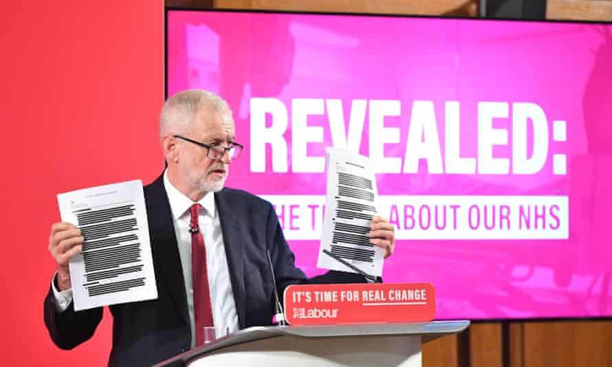 Jeremy Corbyn speaking at a press conference and holding up documents in front of screen reading: 'Revealed: the truth about our NHS'