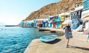 Woman walking in the colorful fishermens village of Klyma, Milos, Greece.