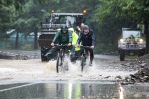 Three cyclists ride through water on flooded highway 54 in Rummenohl, west Germany