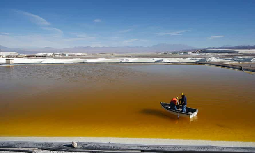 Workers use a boat to take samples from a brine pool at the Rockwood Lithium plant on the Atacama salt flat.