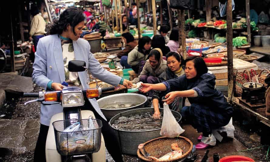 Woman on motorbike buys produce at fish market
