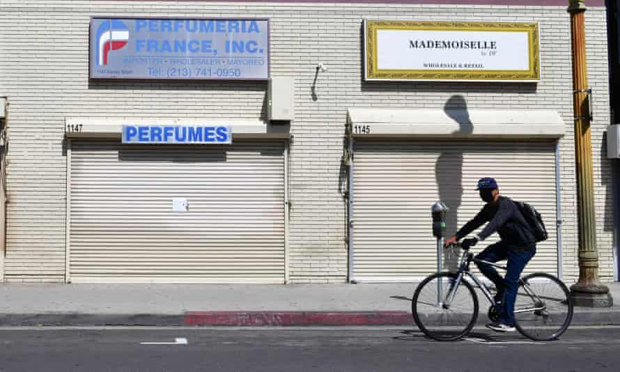 A person bikes past closed stores in Los Angeles, California.
