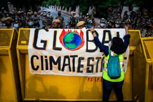 An environmental activist puts a banner on a police barricade during the Fridays for Future strike in New Delhi, India