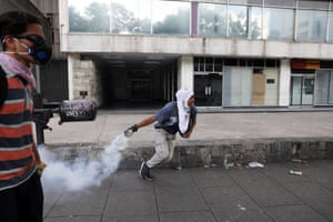 A protesters throws a smoke grenade as thousands take to the streets