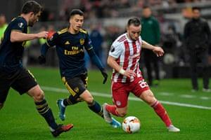 Sokratis Papastathopoulos (left) and Gabriel Martinelli close down Olympiakos' Mathieu Valbuena.