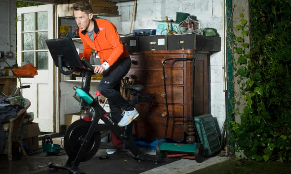 Richard Godwin on his Peloton bike in his garage, wearing an all-weather jacket by Soar (matchesfashion.com), all other clothes are his own.