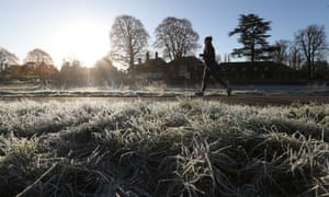 A woman jogs along a frosty path in Cock Marsh, near Cookham, Berkshire.