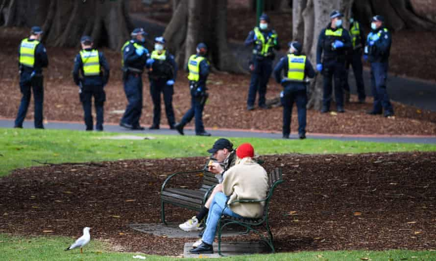 A couple enjoy a break while police patrol through Treasury Gardens in Melbourne over the weekend. During Victoria's first wave of coronavirus, approximately 42% of those fined for breaching gathering rules were under the age of 24.