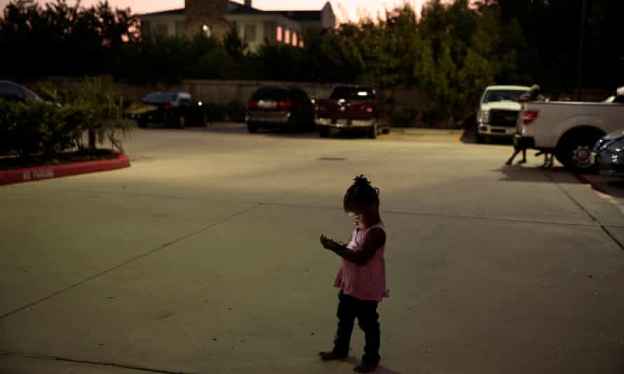 Elizabeth Thomas watches videos on her mother's phone outside their Fema provided hotel room in Houston on 10 September 2017.