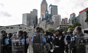 Riot police stand guard as protesters block roads near the Legislative Council in Hong Kong, China.