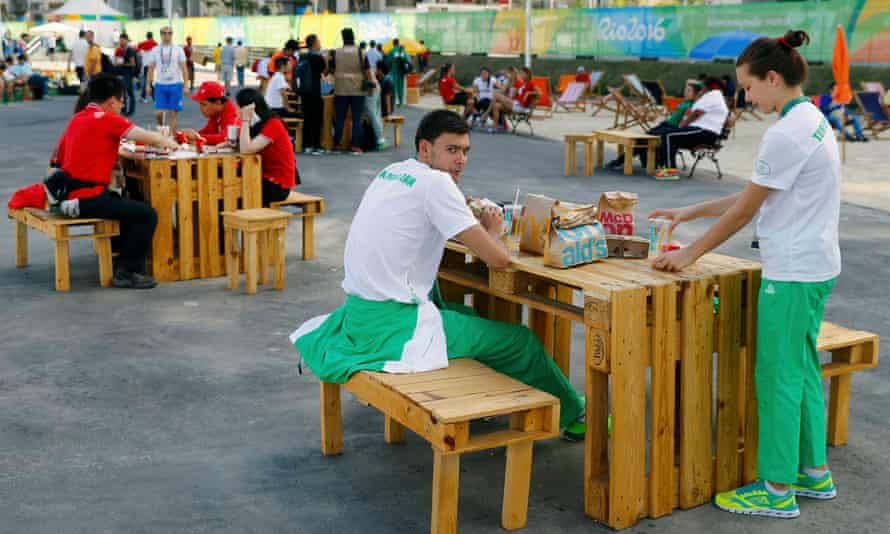 Members of the Turkmenistan team eat McDonald's food inside the Rio Olympic village