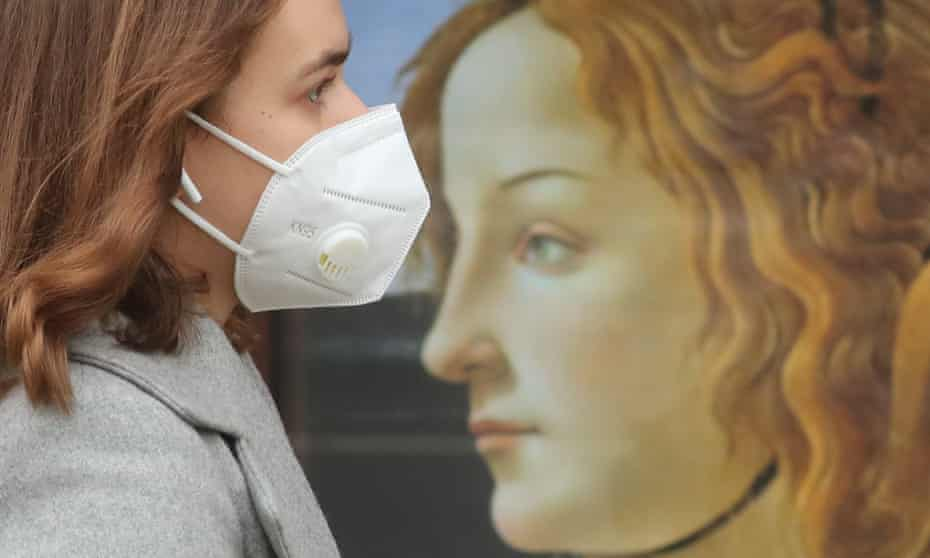 A woman wearing a face mask walks past a mural during the ongoing COVID-19 pandemic