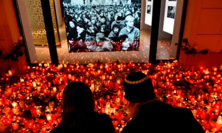 A couple light a candle at a temporary memorial to the Velvet Revolution.