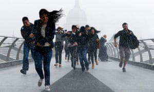 Pedestrians dash through torrential rain along the Millennium Bridge, Southwark, London, as the remnants of Hurricane Bertha swept across parts of the country in August 2014.