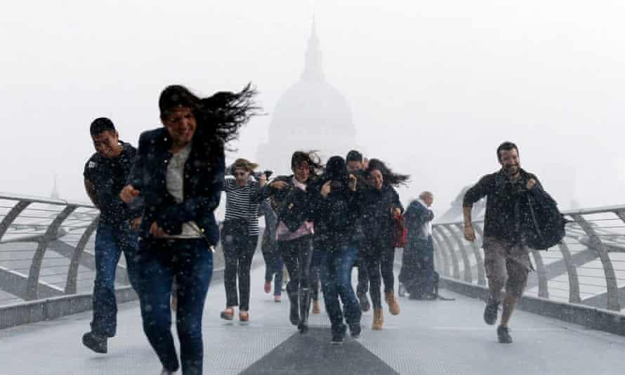 People dash through torrential rain along the Millennium Bridge, Southwark, London, in August 2014.