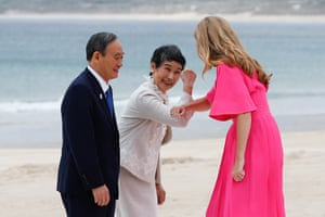 Japan's President Suga watches as his wife, Mariko Suga, bumps elbows with Carrie Johnson