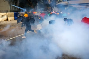 Protesters wearing gas masks hurl teargas canisters back at police