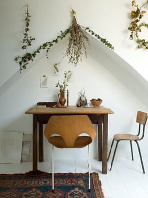 Exploring all the angles: a table and chair under an alcove, with drawings on the wall and Jude's much loved branches.