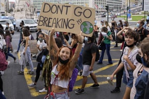 A young woman holds up a poster while taking part in the climate strike in Lisbon, Portugal