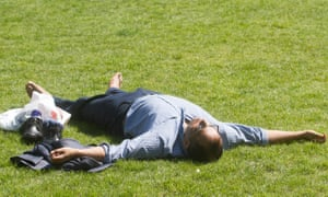 A man lies on the grass in Green Park, central London