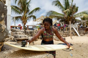 Khadjou waxes her surfboard
