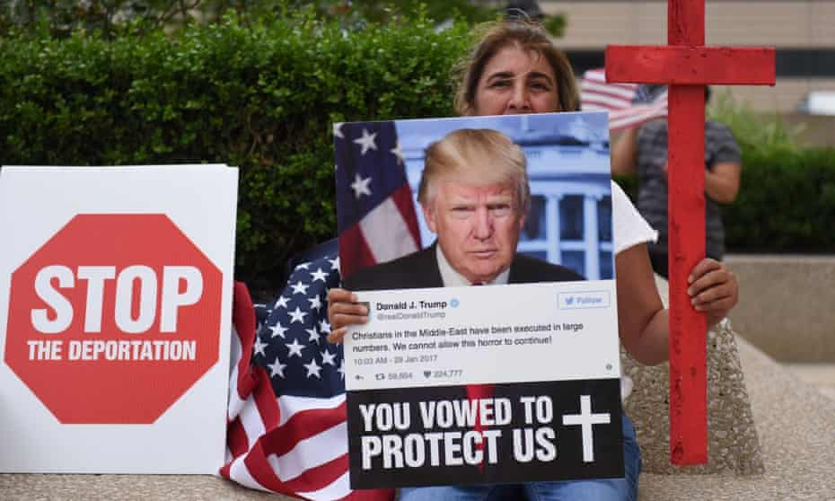 A Chaldean woman holds a photo of Donald Trump during a protest in Detroit.