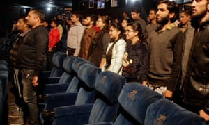 Indian filmgoers stand for the national anthem at a cinema in Jammu