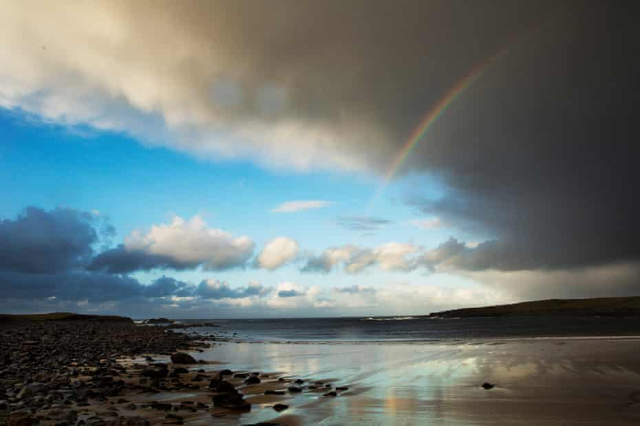 A hail shower sweeps over a beach on Lewis.