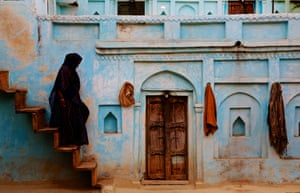 A woman walks down steps wearing a traditional Indian sari.Orchha, Madhya Pradesh, India.