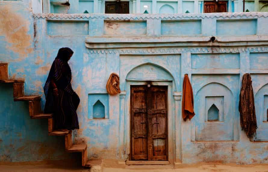 A woman walks down steps wearing a traditional Indian sari.Orchha, Madhya Pradesh, India.