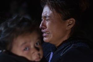 Texas, US. A woman from Guatemala weeps as she carries her child after being smuggled across the Rio Grande river in Roma, Texas