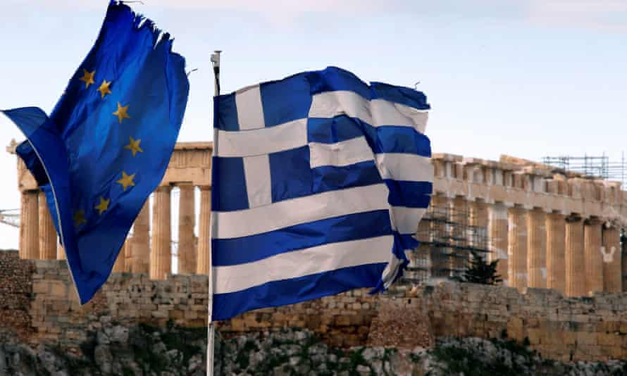 The Parthenon on the Athens Acropolis is seen behind a Greek and an EU flag