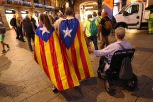 People wearing estelada flags depart following a demonstration for Catalan independence