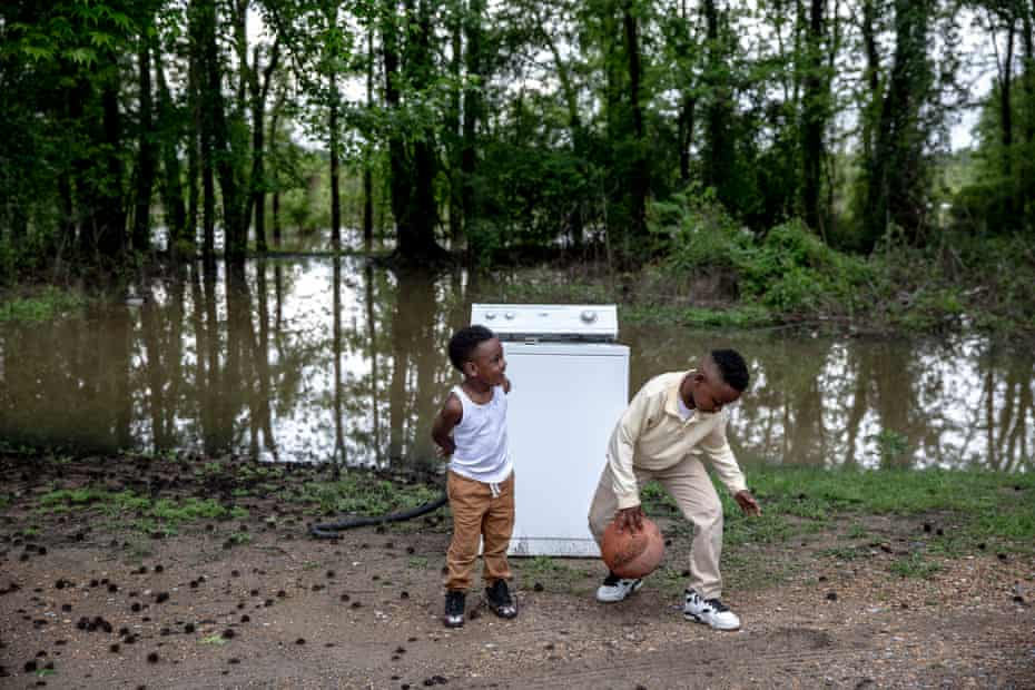 TCHULA, MS - May 9, 2019: August Watts, 3, and his cousin Jaikeem, 7, play with a ball that had been floating in the floodwaters in their backyard. Andrea Morales for The Guardian