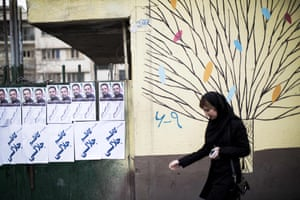 An Iranian woman walks past electoral posters for upcoming parliamentary elections.